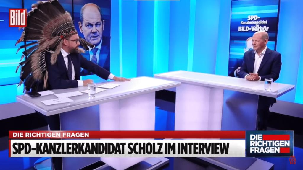 Paul Ronzheimer mit Federschmuck im Gespräch mit Olaf Scholz. (c) Bild